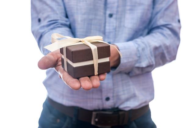 Мужские руки с изолированной подарочной коробкой