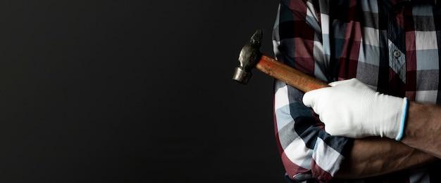 검은 배경과 텍스트 복사 공간이 있는 망치 도구가 있는 남성 손. 배너.