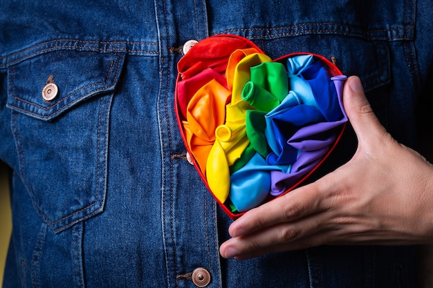 Male hands with heart shaped rainbow lgbtq flag pride month