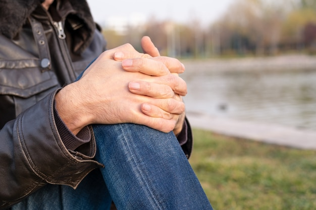 Male hands with interlocked fingers in natural environment