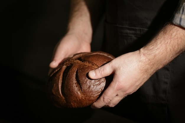 Male hands with loaf of bread on dark background
