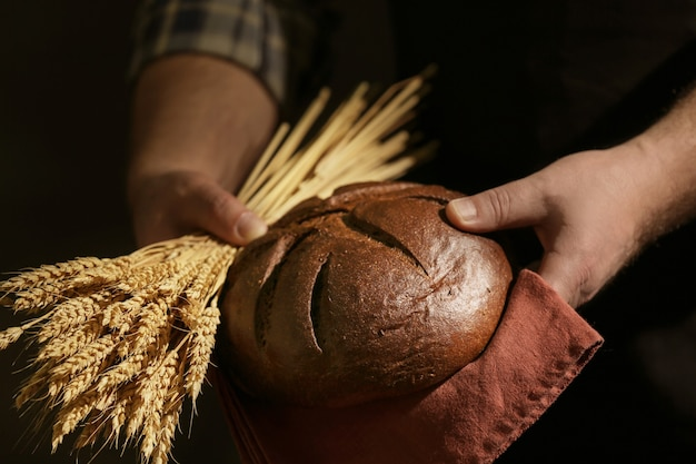 Male hands with loaf of bread and spikelets on dark background, closeup