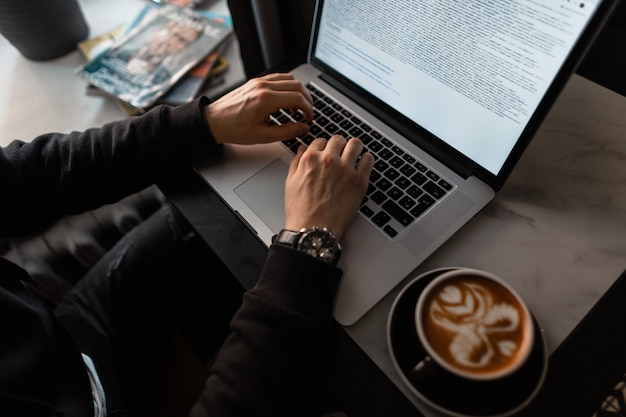 고급 시계를 든 남성 손이 카페의 노트북에 텍스트를 입력하고 있습니다. 전문 프로그래머 남자가 일하고 커피를 마신다