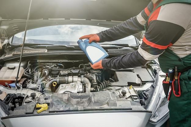 Мужские руки с бутылкой масла над двигателем автомобиля