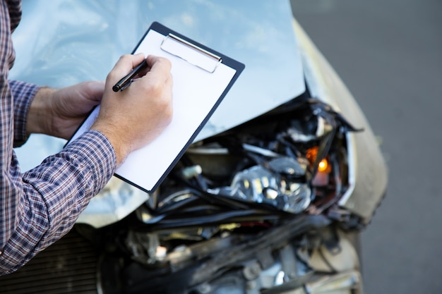 종이가 있는 남성 손은 충돌 교통 사고에서 파괴된 자동차에 대한 자동차 보험 공백을 조롱합니다.