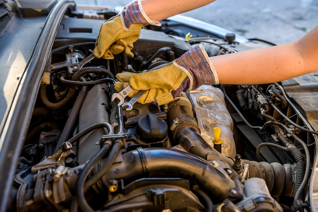 Male hands with spanners. car service concept. hands in protective gloves against car engine