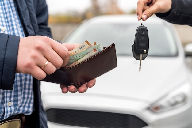 Male hands with wallet and female hands with keys from car