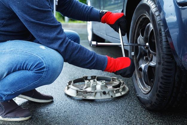렌치와 남성 손입니다. 도로 사고 후 그의 차에 타이어를 바꾸는 남자
