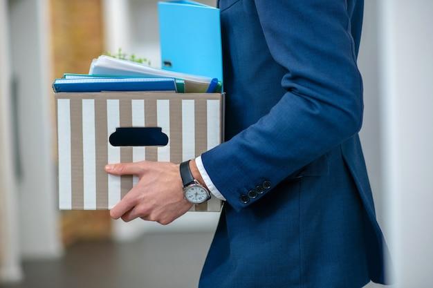 사무실 복도에서 개인 소지품의 줄무늬 상자를 들고 손목 시계와 남성 손