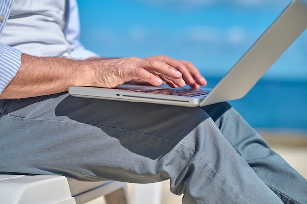 Male hands working on laptop outdoors