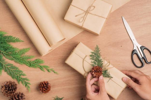 男性の手がクリスマスプレゼントを紙に包み、木製のテーブルの背景に縛り付けます。コピースペースのある上面図