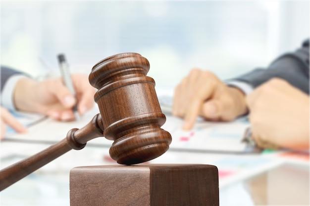 男性の手が書くと背景に木製の裁判官のハンマー
