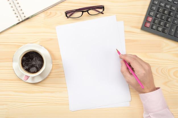木製のテーブルの上に空の白紙に書く男性の手。ドキュメントを扱うビジネスマン。フラットレイ