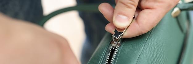 Мужские руки застегивают зеленую кожаную сумку крупным планом
