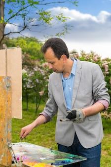 숲에서 미술 수업 중 오일과 아크릴로 가대와 이젤 그림을 작업하는 남성 잘 생긴 중년 명상 예술가
