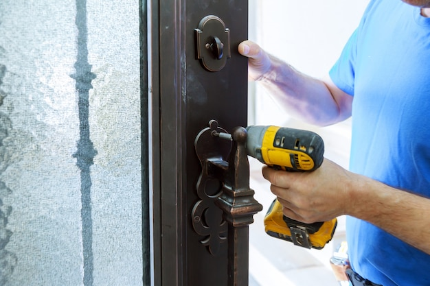 Male handyman carpenter at interior metal door lock installation