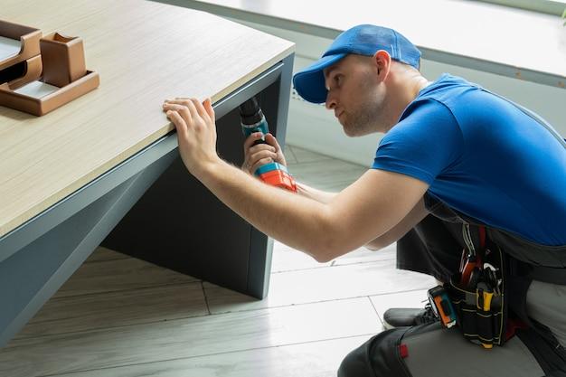 Разнорабочий мужчина с помощью электрической отвертки в руке и ремонтирует деревянный стол