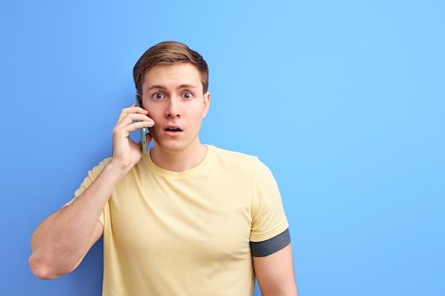 電話で会話したり、誰かと話したり、ニュースを共有したりする男性は、話を聞いている間ショックを受けます。孤立した青い背景