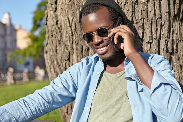 緑の芝生に座って彼のガールフレンドとの楽しい会話を持つ男性