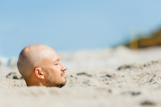 Male head above sand on the beach with body under ground