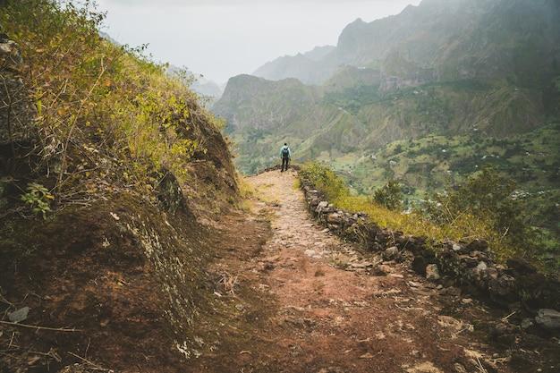 印象的な山の景色を楽しむ男性ハイカー。ラッシュキャニオンバレーははるか下に伸びています。サントアンタン、カーボベルデ。