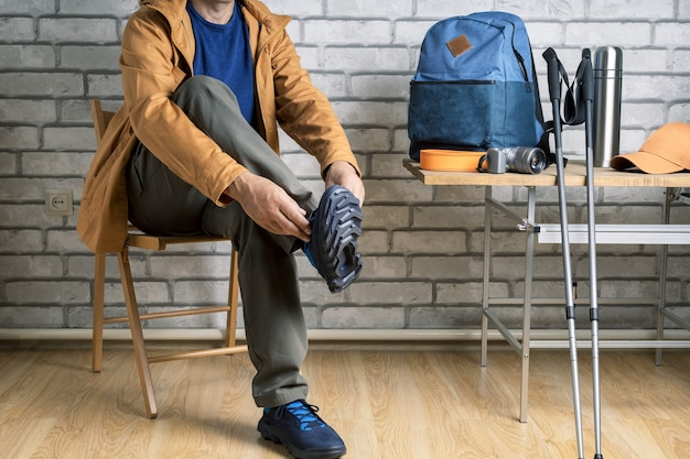 Male hiker getting ready for adventure at home or hotel room.