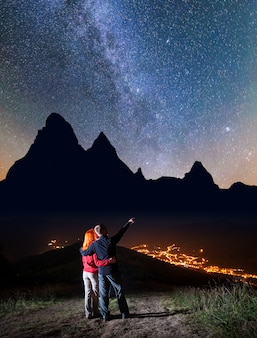 Male hiker hugging red-haired girl and shows on stars