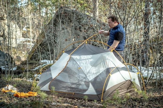 A male hiker is setting up a tent in the forest. concept of tourism, hiking and staying in nature.