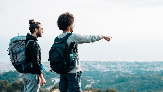 Male hiker looking at african young man pointing finger over the cityscape