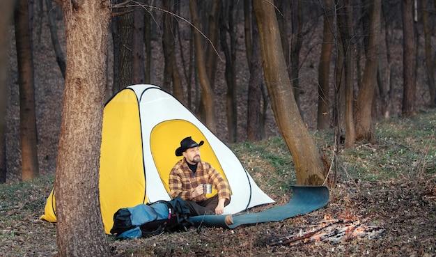 裸の落葉樹林で金属製のマグカップを保持している早春の自然を楽しんでいるテントに座っている男性のハイカー