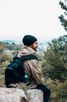 A male hiker sitting on rock with his backpack looking at view