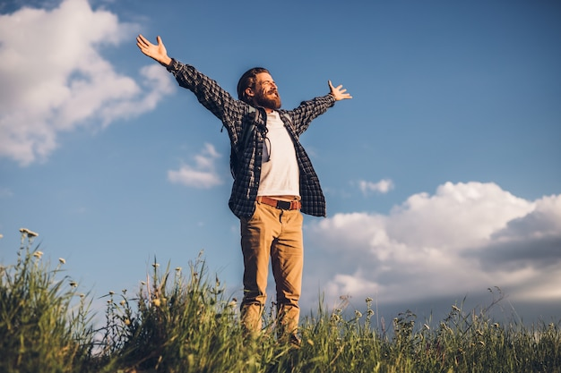 Male hiker spreading hands and enjoying freedom on green field