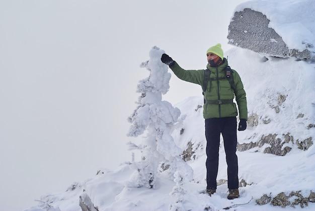 눈보라 동안 산 꼭대기에 서 있는 남성 등산객