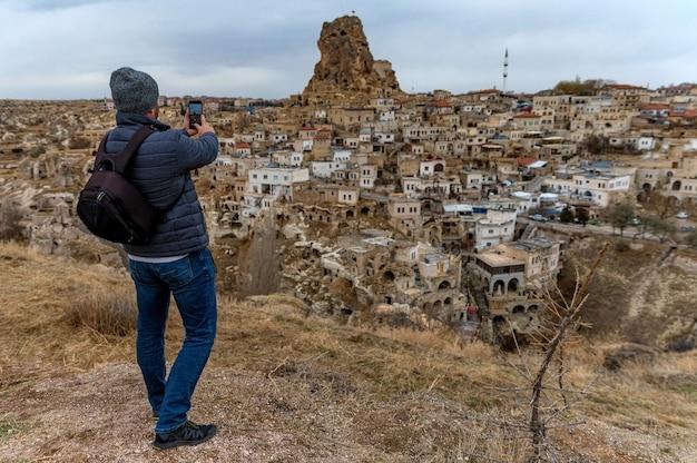 남성 등산객이 유네스코 세계 문화 유산, 카파도키아, 터키의 사진을 찍습니다.