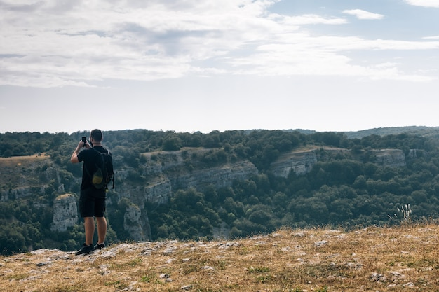 曇り空の下で彼の携帯電話で緑に覆われた丘の写真を撮る男性ハイカー