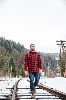森の近くの鉄道を歩く男性ハイカー
