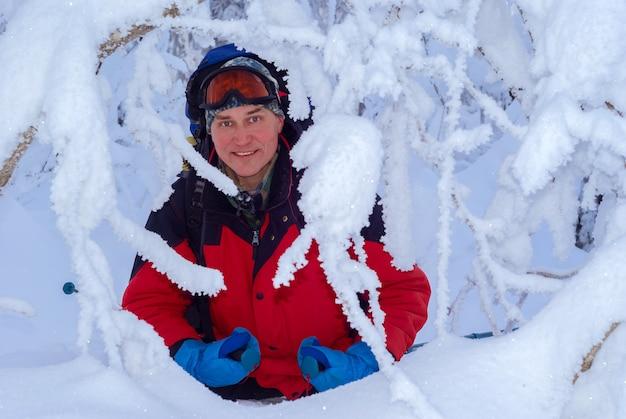 흰 서리 수정으로 덮인 나무 사이 겨울 숲에서 배낭을 메고 있는 남성 등산객