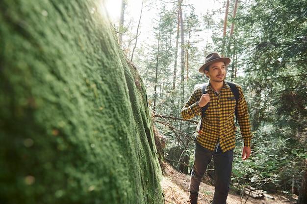 배낭을 메고 숲 속을 걷는 남성 등산객