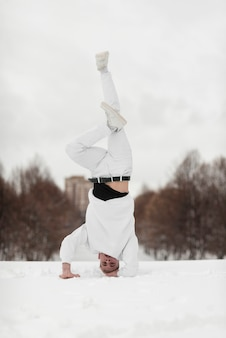 Esecutore hip-hop maschio che sta sulla testa mentre nella neve