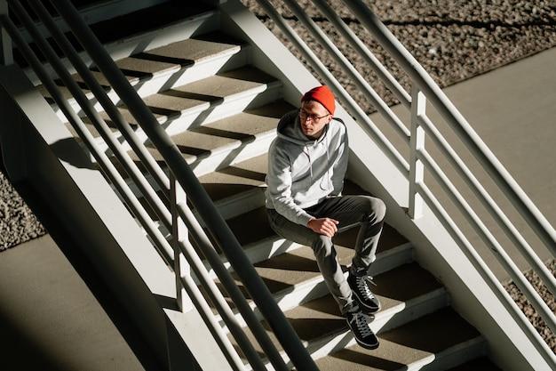 都市の建物の階段で一人で男性のヒップスターは、流行のメガネとストリートファッションの服を着ています