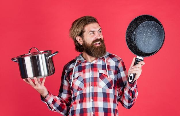 Мужской битник с модными ухоженными волосами и бородой, готовящей на сковороде, готовь.