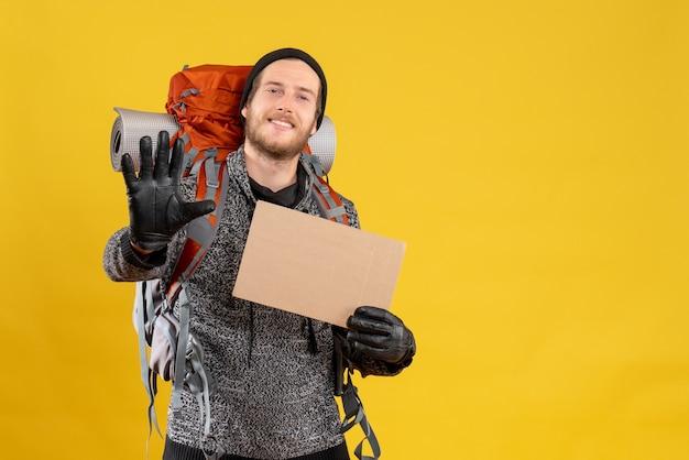 Автостопщик с кожаными перчатками и рюкзаком держит пустой картон, делая знак остановки