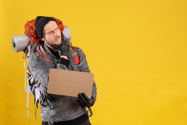 何かを考えている空白の段ボールを保持している革手袋とバックパックを持つ男性のヒッチハイカー