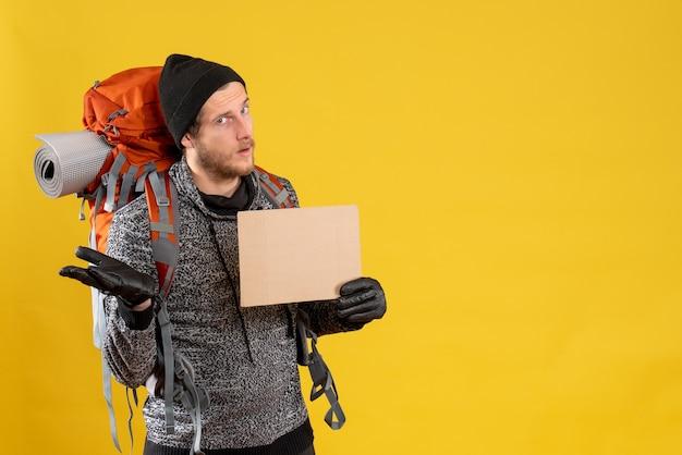 革手袋と空白の段ボールを保持しているバックパックを持つ男性のヒッチハイカー