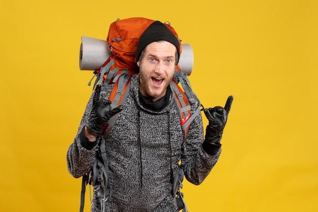 革手袋と岩の看板を作るバックパックを持つ男性のヒッチハイカー