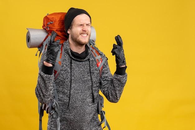Autostoppista maschio con guanti di pelle e zaino che fa segno di desiderio