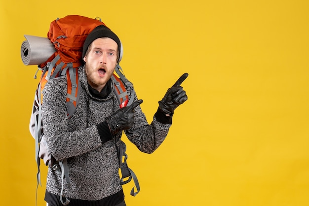 Male hitchhiker with leather gloves and backpack pointing fingers something