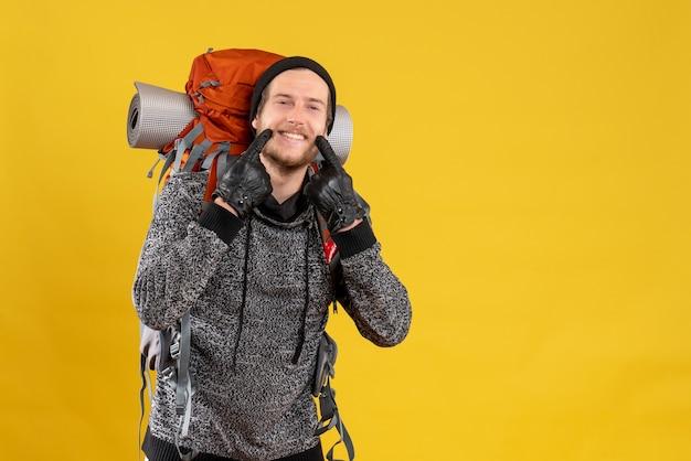 Autostoppista maschio con guanti di pelle e zaino che indica il suo sorriso