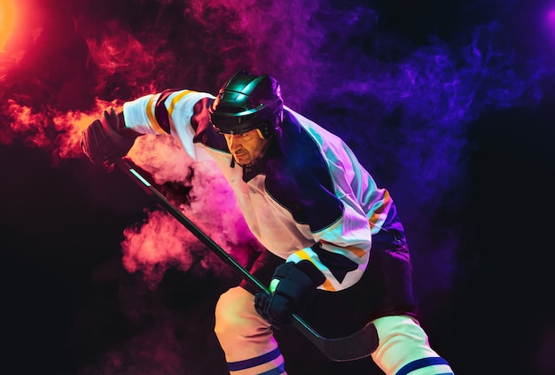 Male hockey player with the stick on ice court and dark neon colored wall