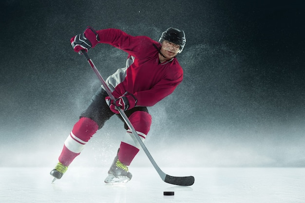 Giocatore di hockey maschio con il bastone sul campo da ghiaccio e muro scuro